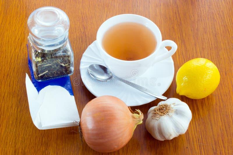 Cup of tea, handkerchiefs, onion, garlic, lemon. A cup of tea with saucer and spoon, lemon, onion, garlic, a glass dose with tea, paper handkerchiefs. Everything stock image