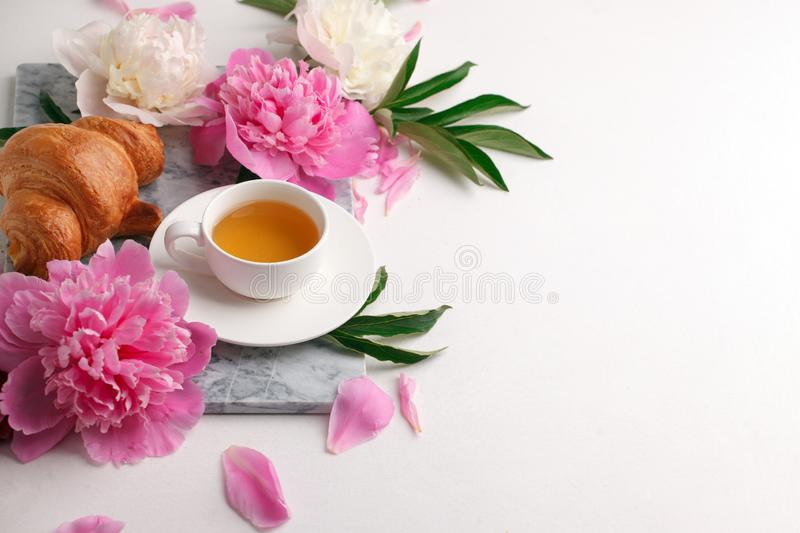 Cup of tea herbal, croissant and peony buds on marble plate on white table. Beauty breakfast composition, celebration seasonal royalty free stock photography