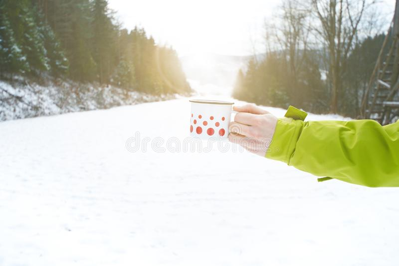 Cup of tea holding in woman hand. Winter background. Hot drink with foam. Snow and cold weather. Coffee break. Concept of drink in stock photography