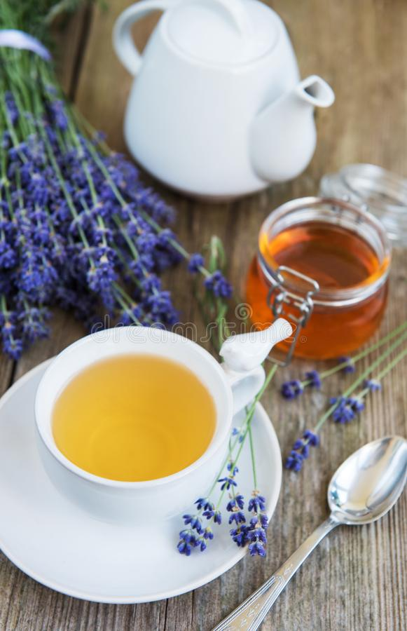 Cup of tea and honey with lavender flowers. On a old wooden table royalty free stock photography
