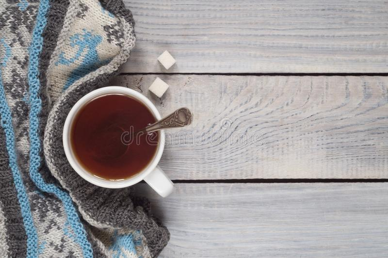 A cup of tea and a knitted scarf on the background of a white wo. A cup of tea and a knitted scarf on the background of white wooden table stock image
