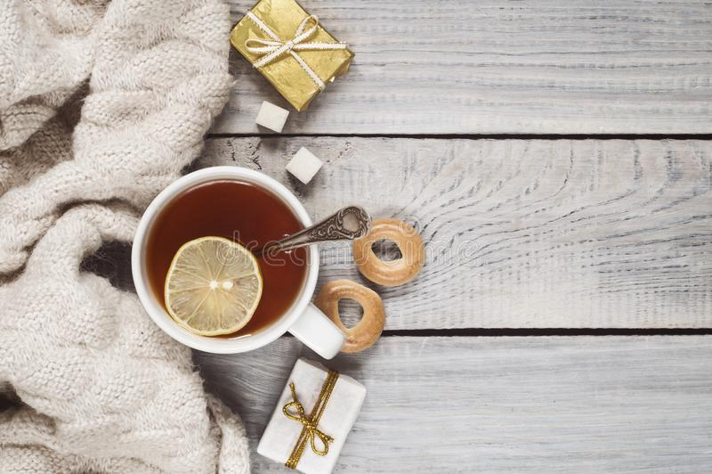 A cup of tea, a knitted scarf and gifts on the background of a w. A cup of tea, a knitted scarf and gifts on the background of white wooden table stock image
