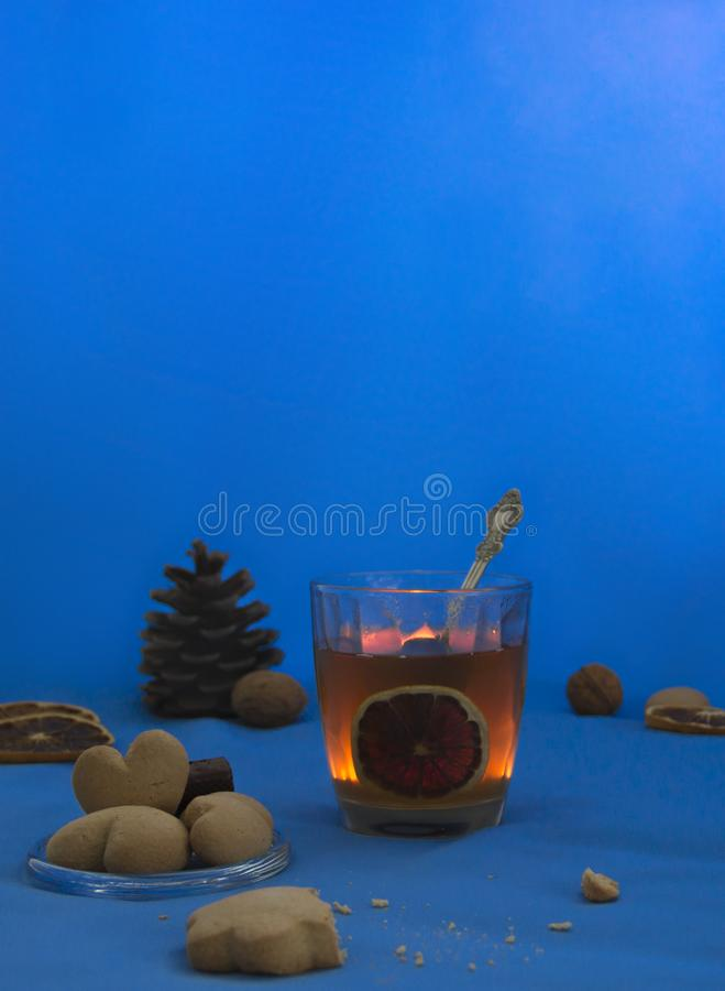 Cup of tea with lemon on a blue background night book cookie candle heart royalty free stock image