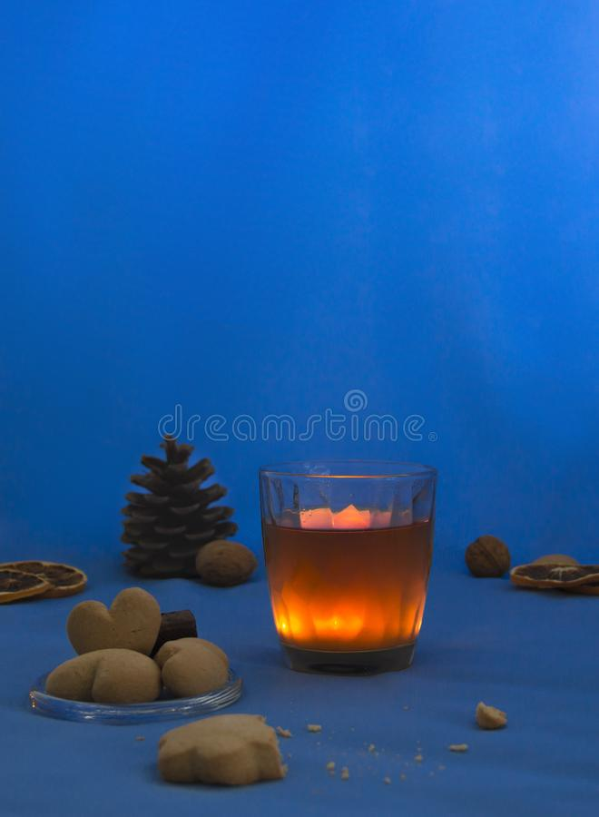 Cup of tea with lemon on a blue background night book cookie candle heart royalty free stock images