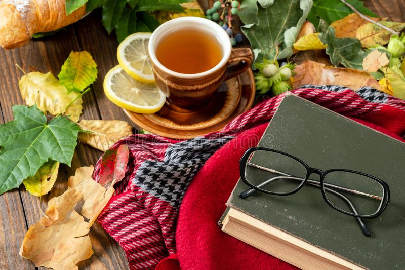 Cup of tea with lemon, croissant, autumn fall leaves, book, glasses, red french berert on wooden background. Cozy home breakfast, stock photo