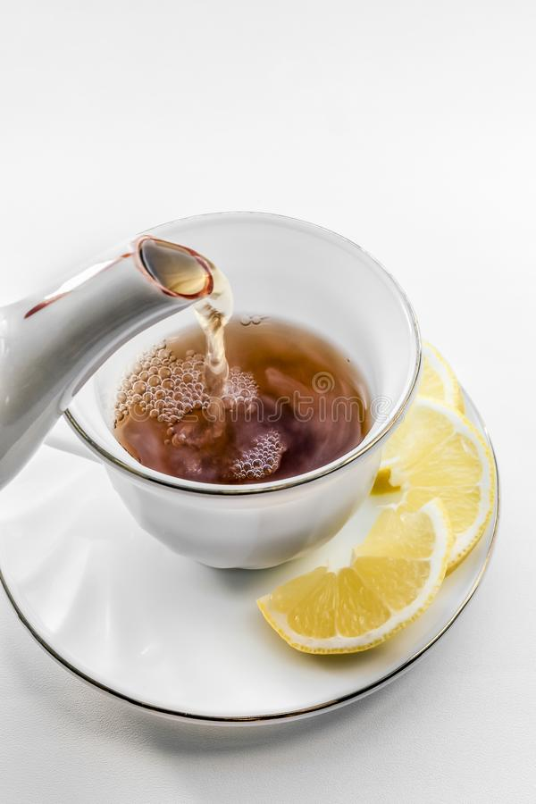 Cup of tea with lemon. Pour tea from teapot into cup stock image