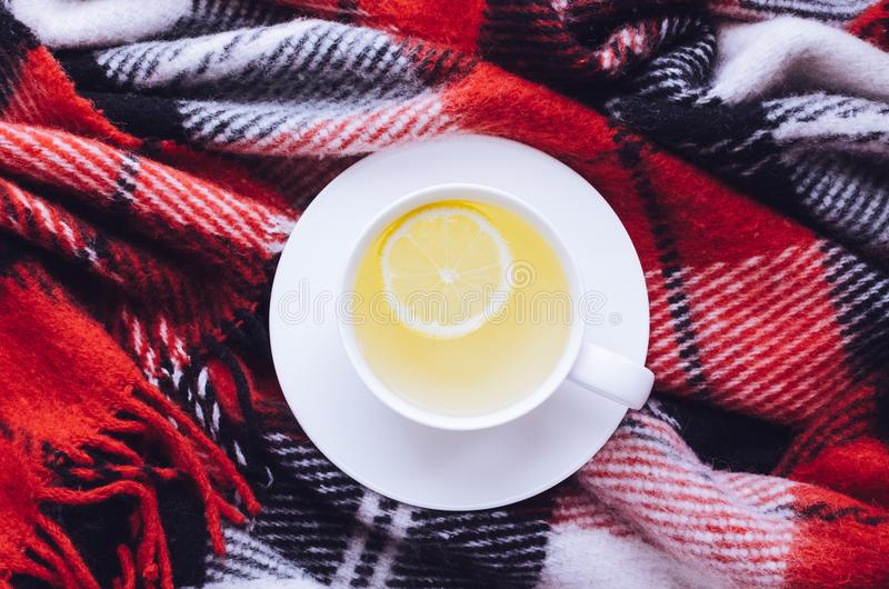 Cup of autumn tea. Cup of tea with lemon on red warm woolen blanket. Hot drink for rainy days. Hygge concept, autumn mood. Cozy winter morning at home. Warm and royalty free stock images