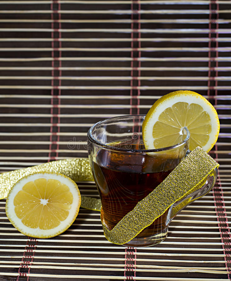 Cup of tea with a lemon wrapped up by a gold tape. A subject drinks royalty free stock photo