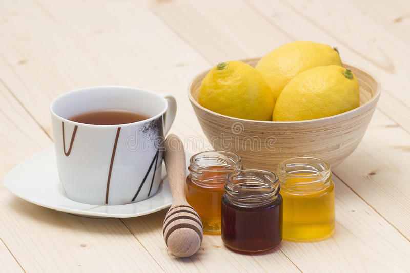 Cup of tea, lemons and honey. Cup of tea, fresh lemons and three jars honey stock image