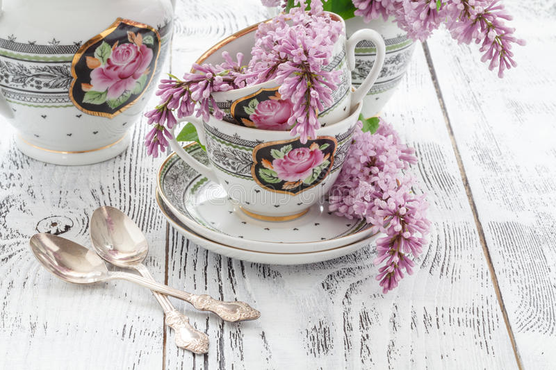 Cup of tea with lilac spring flowers on the wood table. White ba royalty free stock image