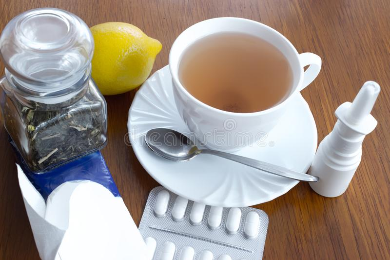 A cup of tea with medicines and a handkerchiefs. A cup of tea with saucer and spoon, lemon, medicines, a glass dose with tea, paper handkerchiefs, nasal drops royalty free stock image