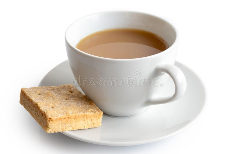 A cup of tea with milk and square shortbread biscuit isolated on stock photo