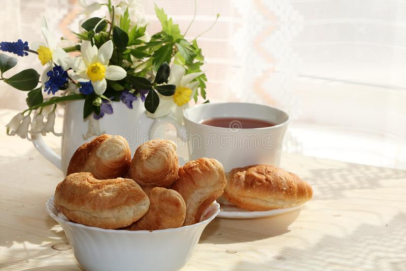 A cup of tea and mini croissants on a sunny table with selective focus, a bouquet of spring. Flowers for mood, diet food and a healthy lifestyle in the village stock images