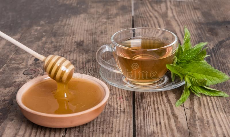 Cup of tea mint honey wooden background. Cup of green tea mint honey on wooden background stock image