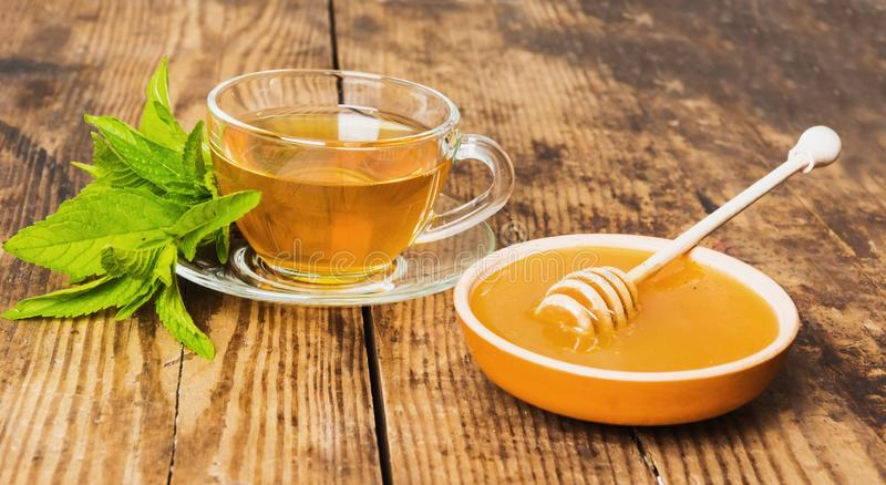 Cup of tea mint honey wooden background. Cup of green tea mint honey on wooden background royalty free stock images