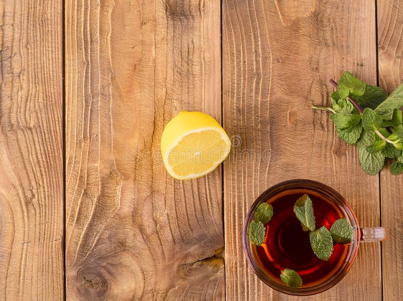 The Cup of tea with mint and lemon on brown wooden table stock photography