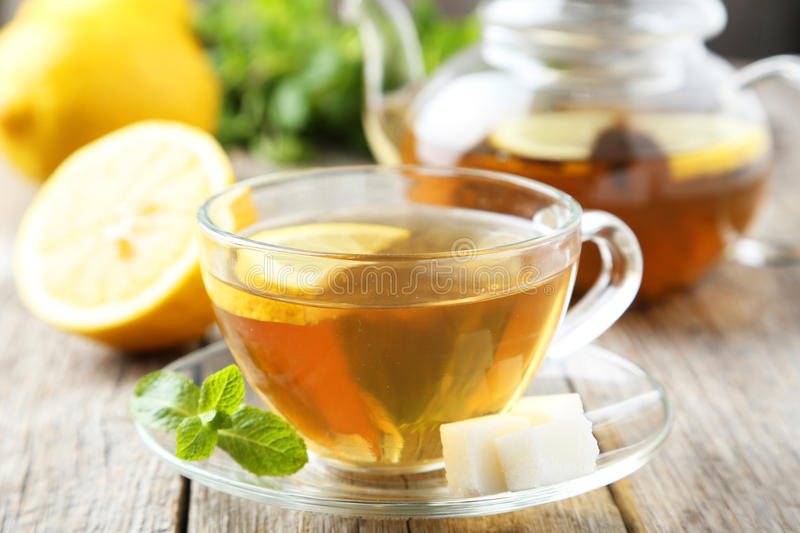 Cup of tea. With mint and lemon on grey wooden background royalty free stock photo