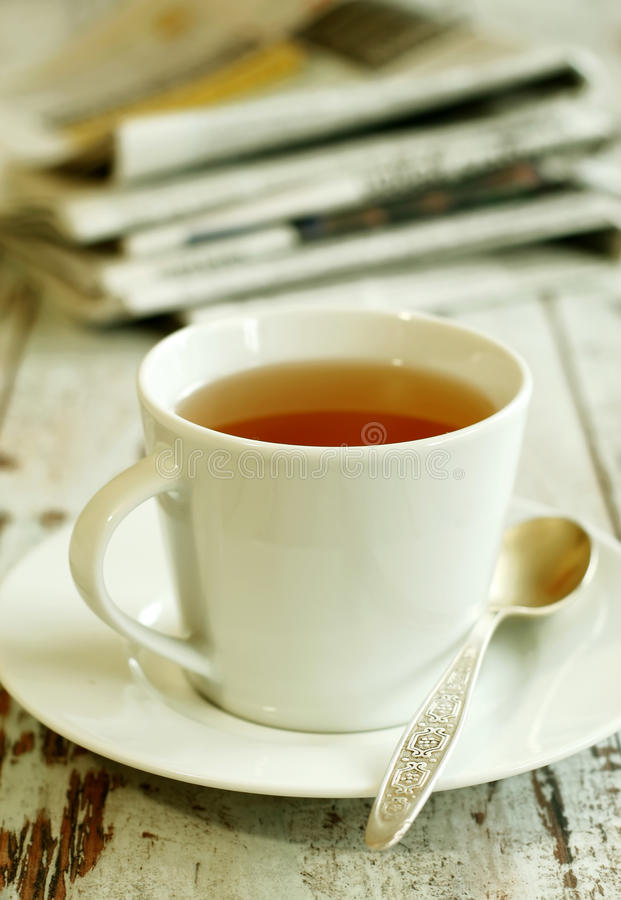 cup of tea and newspaper on old wooden boards royalty free stock photography
