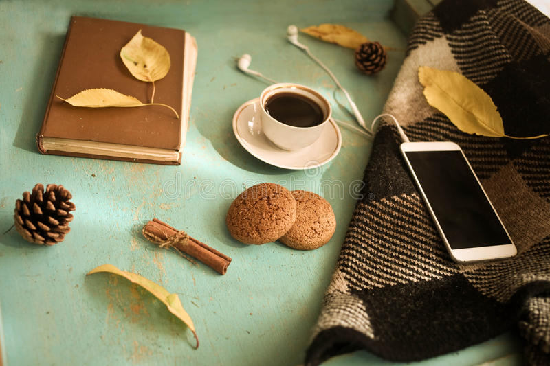 Cup of tea with old book, autumn leaves and oatmeal cookies on w stock images