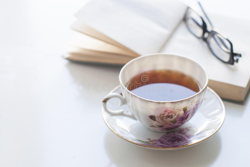 Cup of tea, old book and glasses stock photo