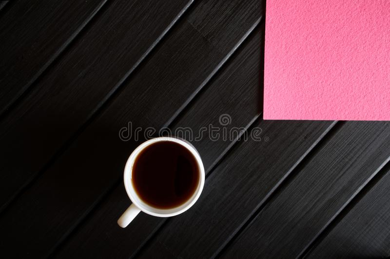 Cup of tea and pink napkin on a black wooden table. View from above. Minimalism royalty free stock photo