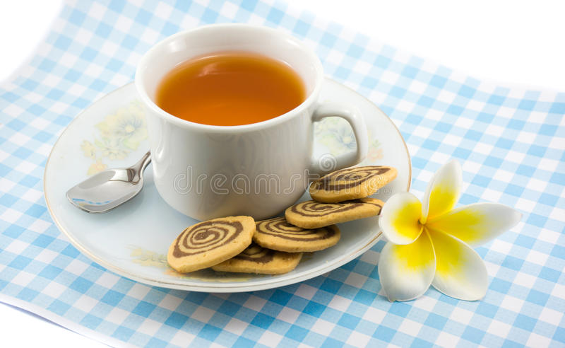 A cup of tea with pinwheel cookies on blue plaid t. Ablemat with plumeria flower with spoon stock images