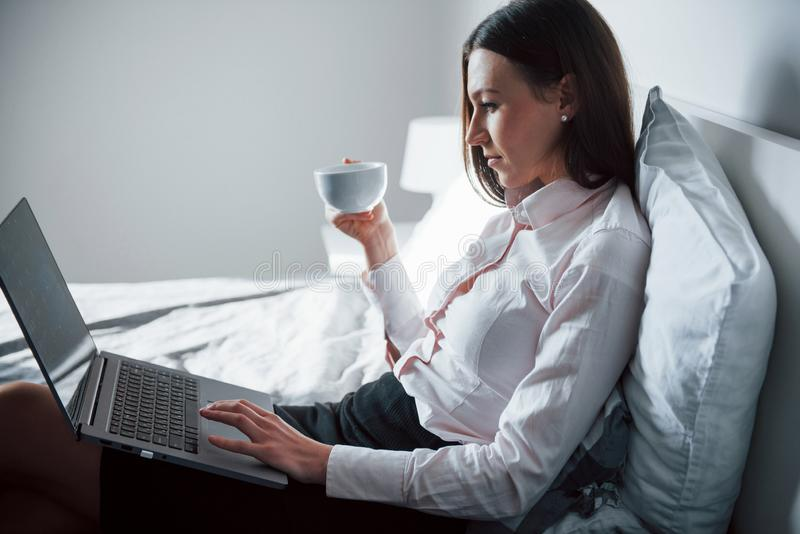 With cup of tea. Pretty young woman lying on the bed at morning time in her room stock photo