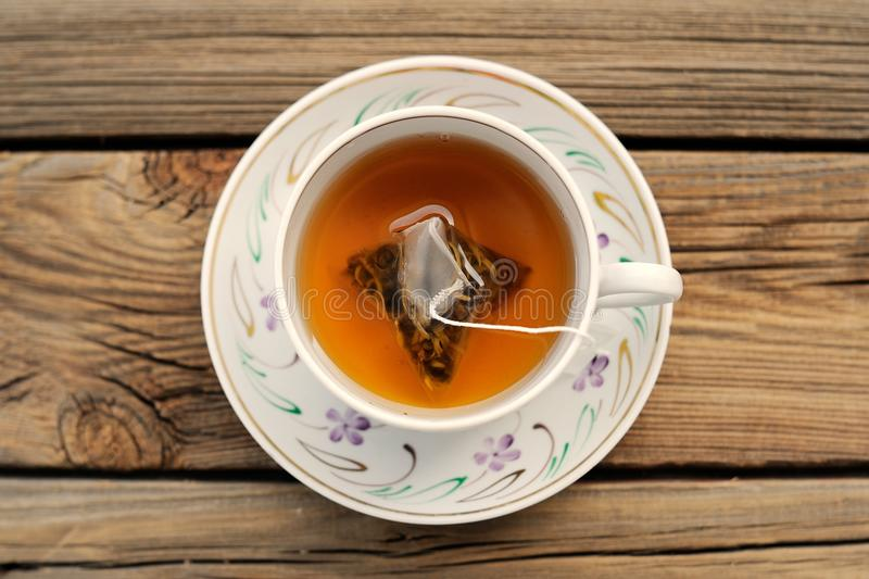 A cup of tea with a pyramid tea bag. On wood board royalty free stock photo