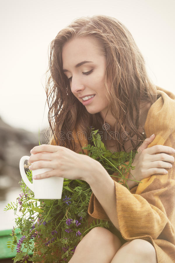 Cup of tea after the rain. Wet and freezing woman in plaid enjoying a cup of tea with herbs after the rain stock photo
