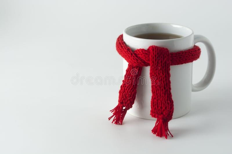 Cup of tea with red knitted scarf.  on white Autumn, fall background. Copy space stock images