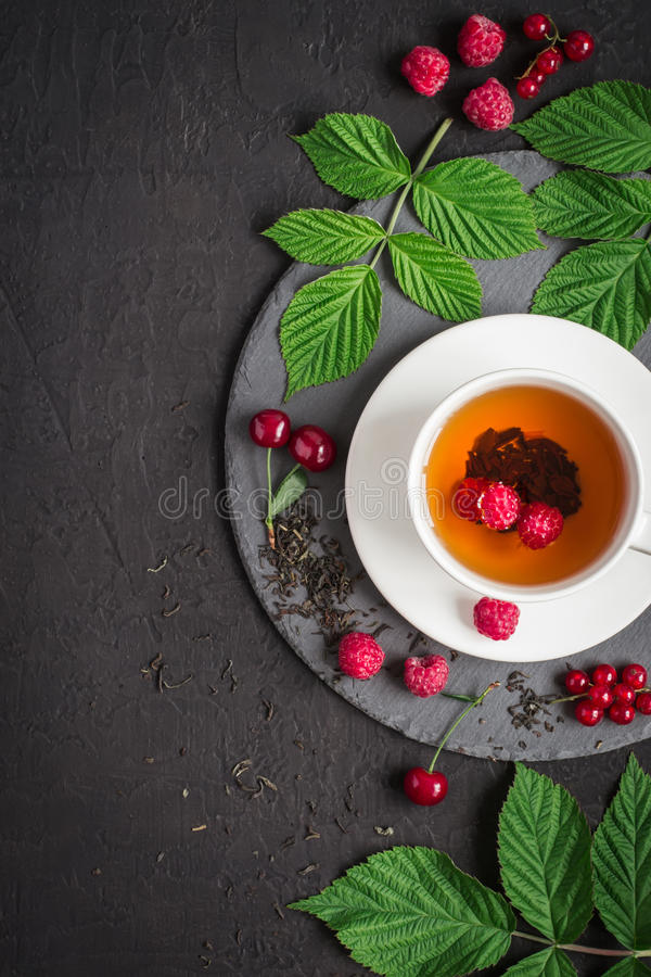 Cup of tea and ripe raspberry, cherry, currant on a black background stock photo