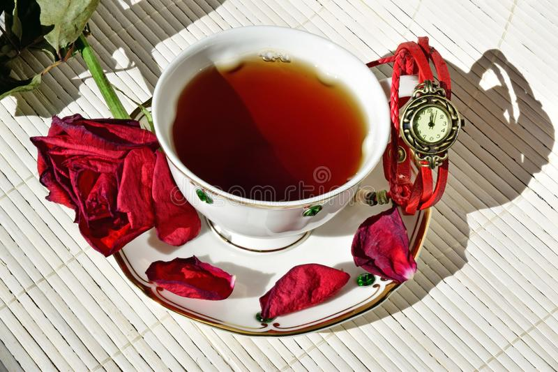 Cup of tea. On the saucer are scattered dry rose petals. royalty free stock photography