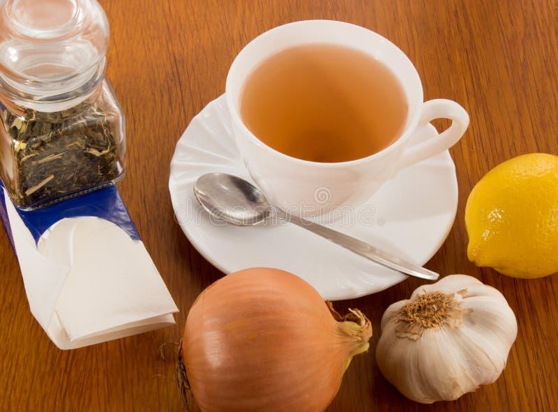 Cup of tea, handkerchiefs, onion, garlic, lemon. A cup of tea with saucer and spoon, lemon, onion, garlic, a glass dose with tea, paper handkerchiefs. Everything stock photos
