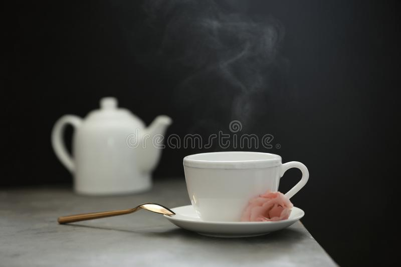 Cup of tea, saucer and spoon on table. Against dark background royalty free stock images