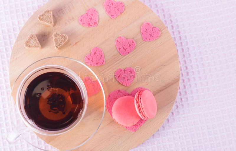 A cup of tea and a saucer with strawberry cookies along with sugar hearts and pink hearts on a light round wooden tray royalty free stock photo