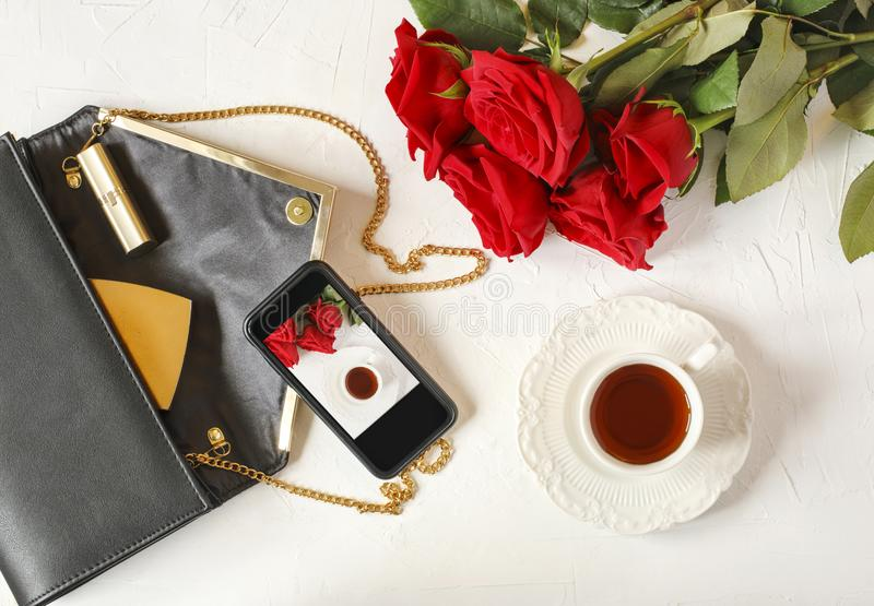 Cup of tea, woman`s bag and red roses on white background. Flat royalty free stock image