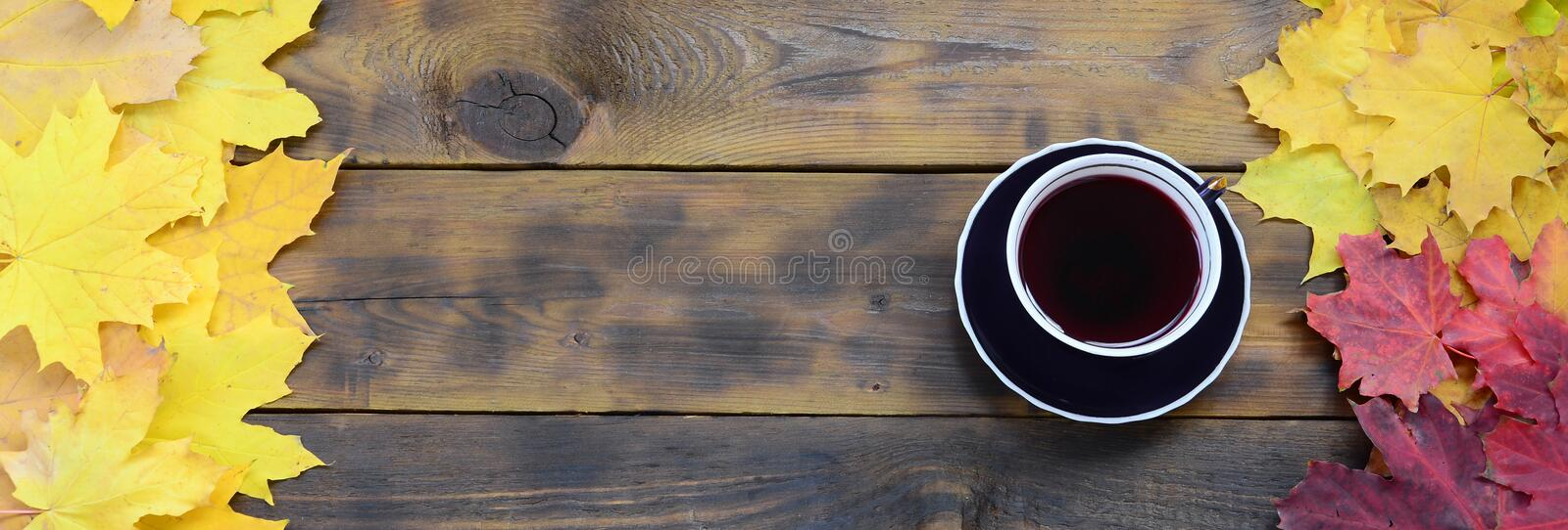 A cup of tea among a set of yellowing fallen autumn leaves on a background surface of natural wooden boards of dark brown colo. R royalty free stock images