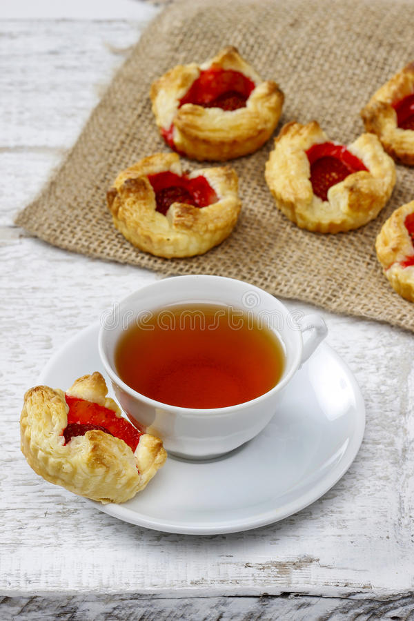 Cup of tea and small cakes on wooden rustic table royalty free stock image