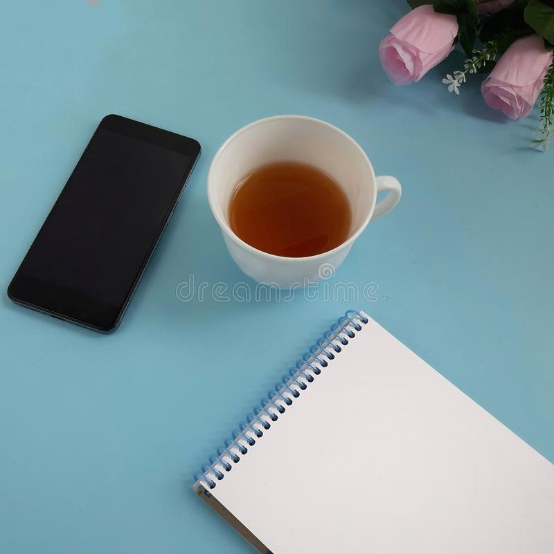 Cup of tea, smartphone, blank notepad, roses on blue background. royalty free stock photography