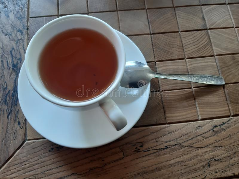 A cup of tea with a spoon on the table in a cafe. A cup of tea with a spoon on the table beverage closeup traditional natural fresh organic sweet brown delicious royalty free stock images