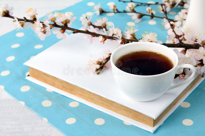 Cup of tea and a sprig. Flowering branch of peach with a Cup of strong tea with a book on the polka dot on white wooden background royalty free stock photography