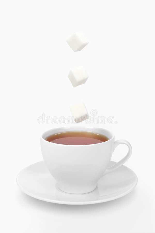 Cup of tea and sugar cubes stock images