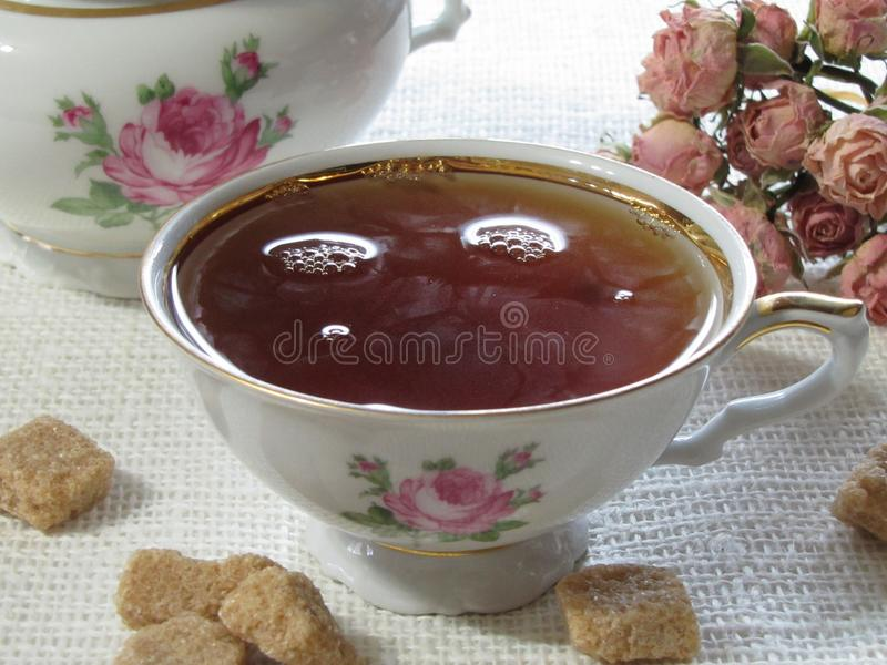 Cup of tea on the table. Tea Cup with brown lump sugar stock image