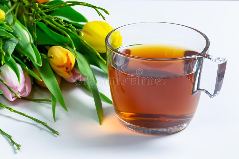 A cup of tea on a table with tulip flower bouquet royalty free stock image