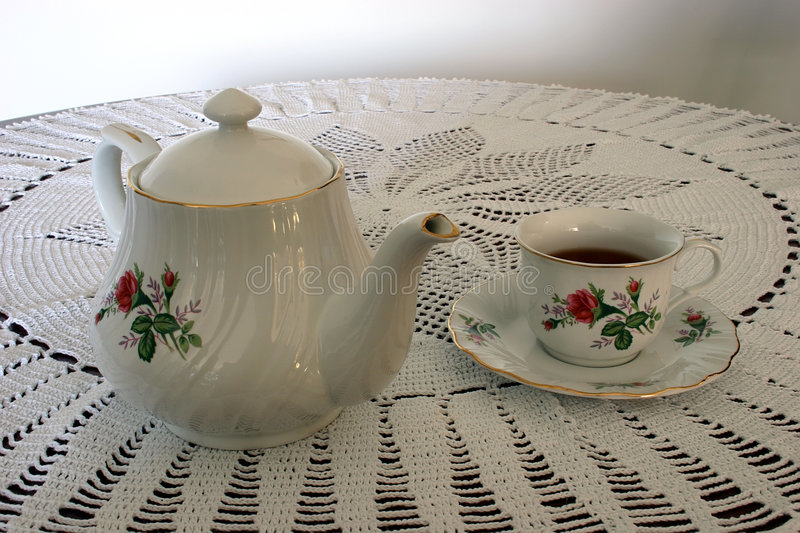 Cup of Tea and a Tea Pot. This a tea pot and a cup of tea sitting on a crocheted lace tablecloth stock photos