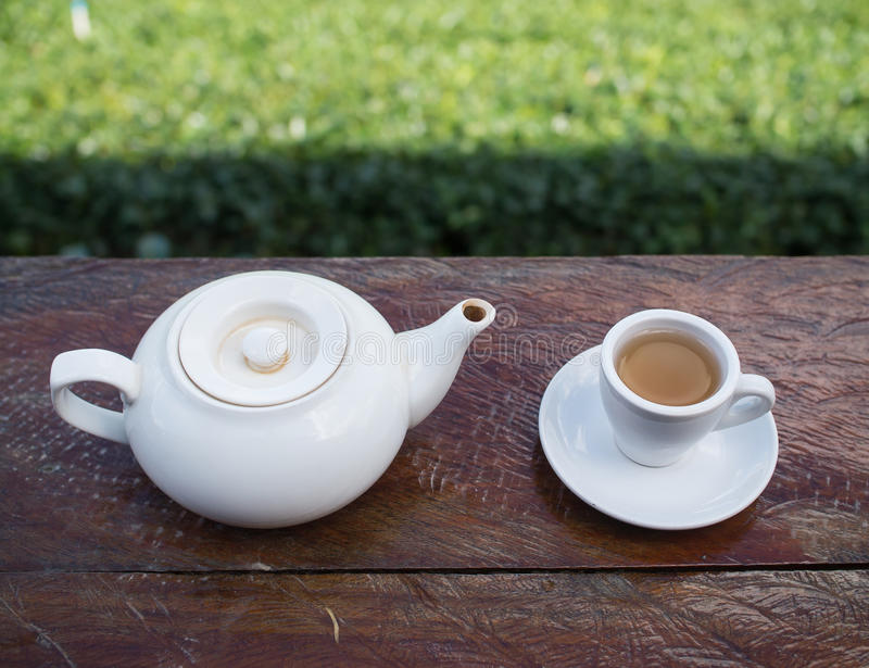 Cup of tea and teakettle on wooden bar. Top shot - Cup of tea and teakettle on wooden bar. Beauty nature background of tea plantation at Doi-Montngo , Chiang Mai stock image