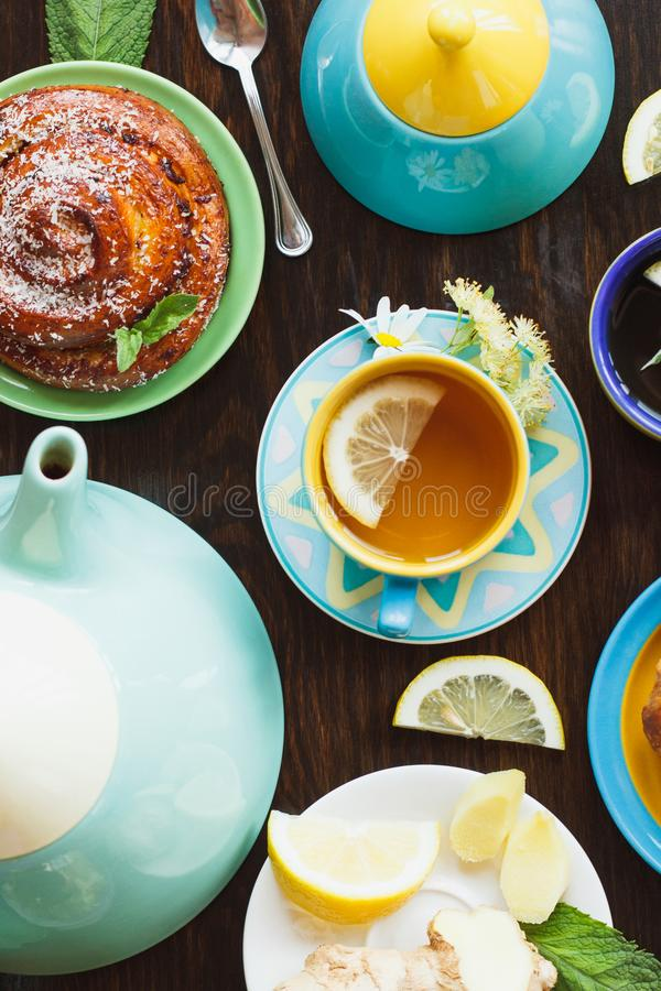 Cup with tea, teapot and baked goods. Teapot, cup of herd tea with lemon and baked goods on the wooden background, top view stock images