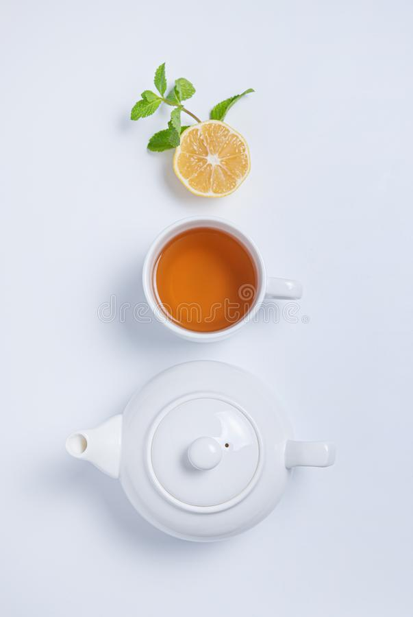 Cup of tea and teapot with lemon and mint on  white background. Top view and copy space stock photos