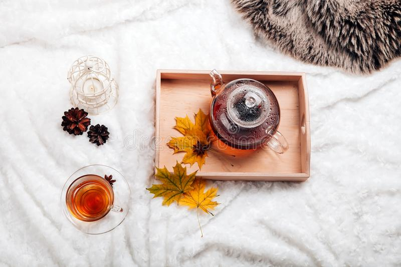 Cup of tea and teapot in wooden tray on the bed. Warm sweater, candles, yellow leaves. The concept of cozy autumn weekend house. stock photos