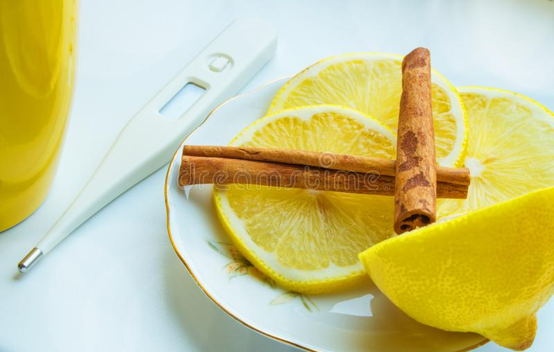 Cup of tea, thermometer, and the lemon with cinnamon - remedy for colds. Cup of tea, a thermometer, and the lemon with cinnamon - remedy for colds royalty free stock photography
